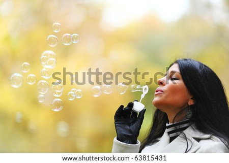 autumn woman blow bubbles