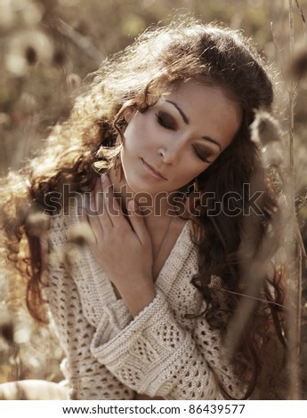 autumn woman closeup portrait with nature on the background - stock photo
