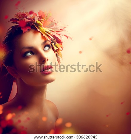 Autumn Woman Fashion Art Portrait. Beauty Romantic Autumn Girl with colorful yellow and red Leaves on her Head. Hairstyle and Makeup. Fall. Fashion Model closeup