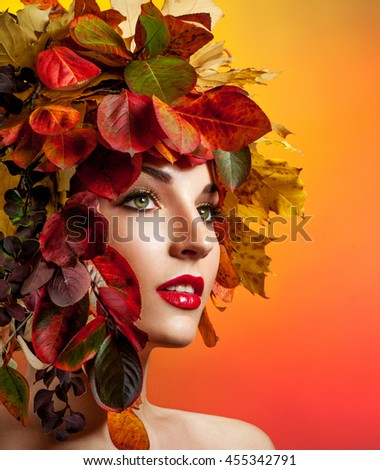 Autumn Woman Fashion Portrait. Beautiful Model Girl with colourful autumn leaves hairstyle. Autumn leaves Hair. - stock photo
