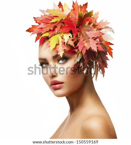 Autumn Woman Fashion Portrait. Beauty Autumn Girl with colorful yellow and red Leaves on her Head. Creative Hairstyle and Makeup. Fall. Glamour Fashion Model closeup