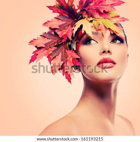 Autumn Woman Fashion Portrait. Beauty Autumn Girl with colorful yellow and red Leaves on her Head. Hairstyle and Makeup. Fall. Glamour Fashion Model closeup