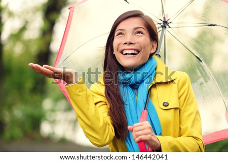 Autumn woman happy after rain walking with umbrella. Female model looking up at clearing sky joyful on rainy fall day wearing yellow raincoat outside in nature forest by lake. Multi-ethnic Asian girl. - stock photo