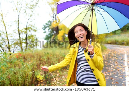 Autumn woman happy in rain running with umbrella. Female model looking up at clearing sky joyful on rainy fall day wearing yellow raincoat outside in nature forest by lake. Multi-ethnic Asian girl. - stock photo