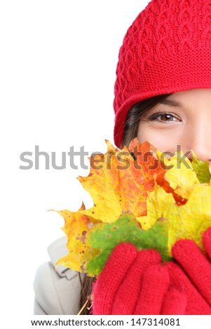 Autumn woman happy with colorful fall leaves isolated on white background in studio. Cheerful girl hiding behind autumn leaves. Portrait close up of multiracial mixed race Asian Caucasian female model - stock photo
