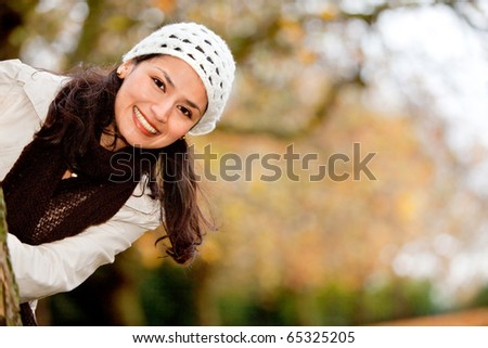 Autumn woman having fun at the park and smiling