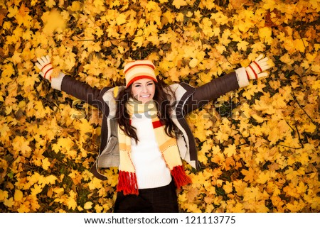 autumn woman lying over leaves and smiling, top view - stock photo