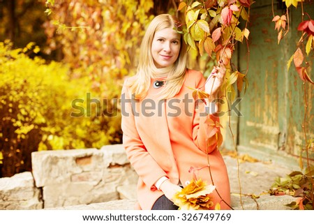 Autumn woman on background fall landscape leaves of trees. Model on autumn season. Fashion people.