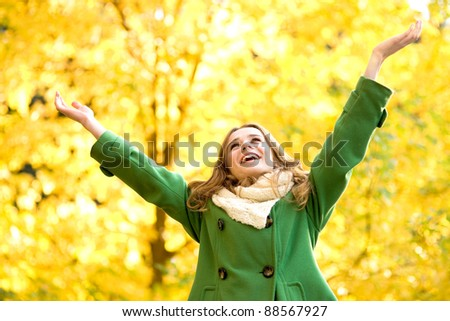 Autumn woman standing with arms raised - stock photo