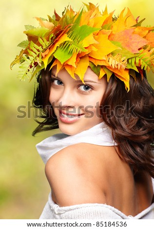 Autumn woman with crown of fall maple leaves - stock photo