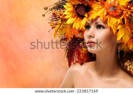 Autumn Woman with Decorated Hairstyle. Portrait of Fashion Girl with Fall Leaves