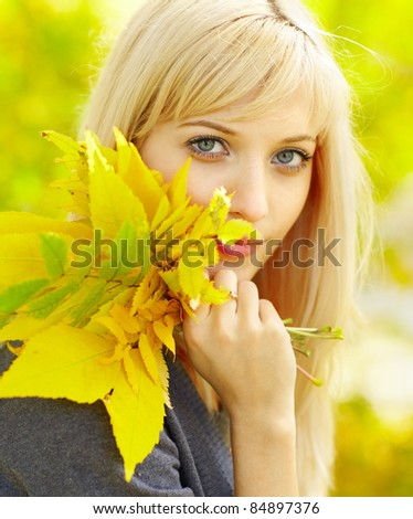 Autumn woman with yellow fall maple and fern leaves - stock photo