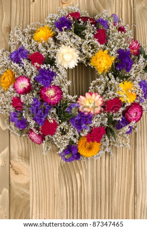 Autumn wreath with dried flowers on a wooden background - stock photo