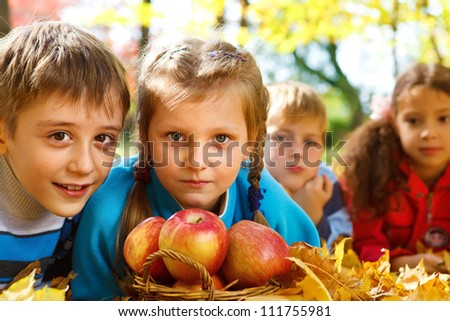 Autumnal apples in basket and kids beside it - stock photo