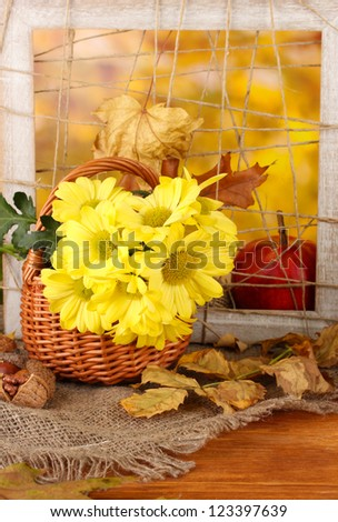 Autumnal composition with flowers in basket  and leaves on bright background