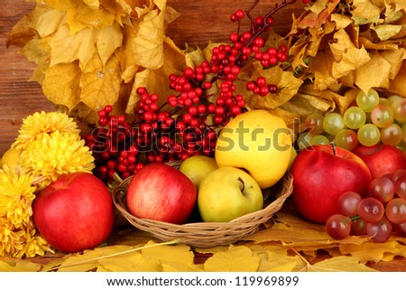 Autumnal composition with yellow leaves, apples and mushrooms on wooden background