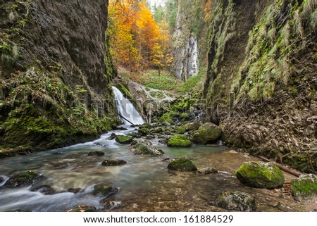 Autumnal creek with beautiful mossy stones and blue water in Transylvania - stock photo
