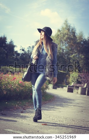 Autumnal fashion of women. Attractive young stylish model posing outdoors. Fashionable girl wearing trendy clothes walking in park.