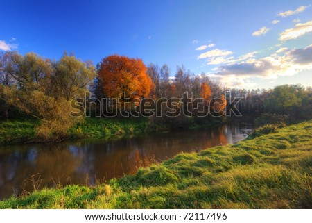Autumnal field under blue sky - stock photo