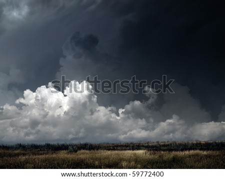 Autumnal field under dark thunderstorm sky. - stock photo