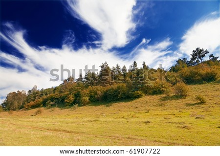 Autumnal hill and wonderful blue sky with clouds.