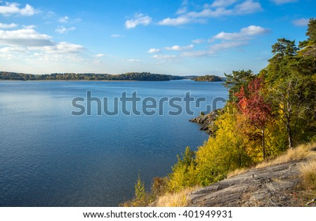 Autumnal lake shore with forest under sky. Trees on rock coast of rippling lake in autumn sunny day. Beautiful panoramic landscape with yellow trees on big stones and lake. Place for your own text - stock photo