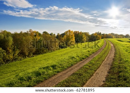Autumnal landscape with green grass, road and clouds. - stock photo