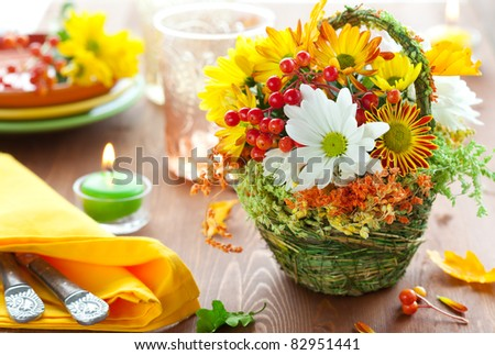 autumnal place setting with basket of autumn flowers - stock photo