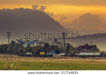 Autumnal rural landscape with remote houses and Piatra Craiului mountains at sunset in Brasov county, Transylvania region, Romania. - stock photo