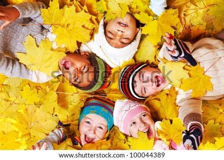 Autumnal screaming kids group in yellow leaves - stock photo