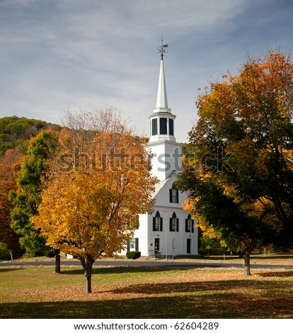 Autumnal shot of the typical Vermont church in fall as the bright trees turn orange and red - stock photo