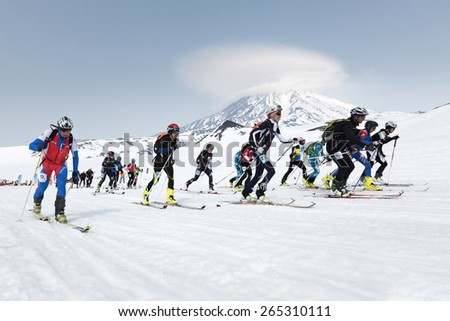 AVACHA, KORYAK VOLCANOES, KAMCHATKA, RUSSIA - APRIL 27, 2014: Mass start race, ski mountaineers climb on skis on mountain. Team Race ski mountaineering Asian, ISMF, Russian, Kamchatka Championship. - stock photo