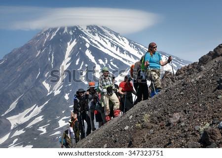 AVACHA VOLCANO, KAMCHATKA PENINSULA, RUSSIA - JULY 08, 2014: Hiking on Kamchatka - a group of tourists go hiking and climbing to the top of Avachinsky Volcano on background of Koryaksky Volcano. - stock photo
