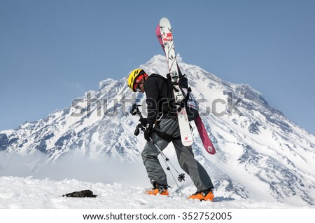 AVACHA VOLCANO, KAMCHATKA, RUSSIA - APR 21, 2012: Open Cup of Russia on ski-mountaineering. Ski mountaineer climbing on mountain with skis strapped to backpack on background active Koryaksky Volcano.