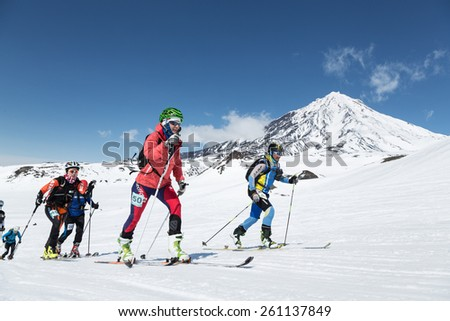 AVACHA VOLCANO, KAMCHATKA, RUSSIA - APRIL 26, 2014: Group of ski mountaineer climb on skis on background volcano. Individual race ski mountaineering Asian, ISMF, Russian and Kamchatka Championship. - stock photo