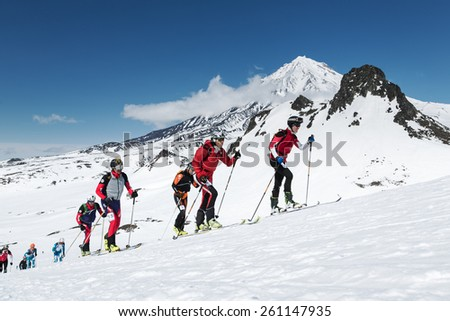 AVACHA VOLCANO, KAMCHATKA, RUSSIA - APRIL 26, 2014: Group ski mountaineer climb on skis on background volcano. Individual race ski mountaineering Asian, ISMF, Russian and Kamchatka Championship. - stock photo