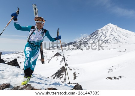 AVACHA VOLCANO, KAMCHATKA, RUSSIA - APRIL 26, 2014: Japanese ski mountaineer Tsuda Kei climbs mountain on background of Koryak Volcano. Ski mountaineering Asian, ISMF, Russian, Kamchatka Championship. - stock photo