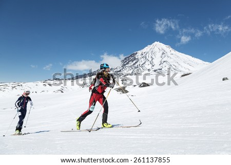 AVACHA VOLCANO, KAMCHATKA, RUSSIA - APRIL 26, 2014: Ski mountaineers climbs on skis on background volcano. Individual race ski mountaineering Asian, ISMF, Russian and Kamchatka Championship. - stock photo