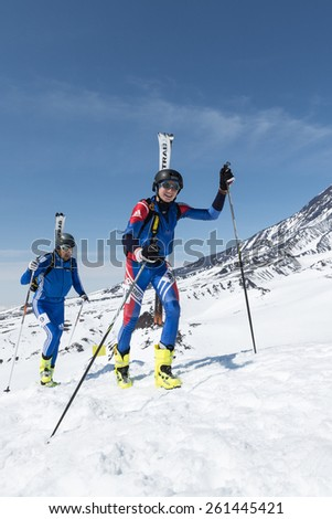 AVACHA VOLCANO, KAMCHATKA, RUSSIA - APRIL 26, 2014: Sportsmans Amangaliev Vladimir and Baranov Denis climb on volcano. Individual race ski mountaineering Asian, ISMF, Russian, Kamchatka Championship. - stock photo