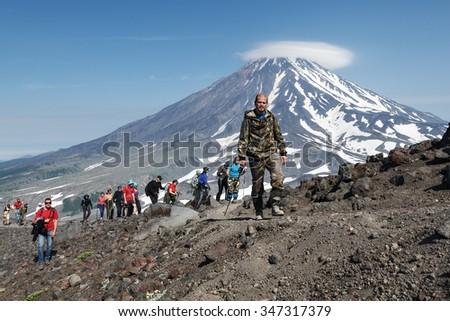 AVACHA VOLCANO, KAMCHATKA, RUSSIA - JULY 08, 2014: Hiking on Kamchatka Peninsula - a group of tourists climbing to top of Avacha Volcano on a background of Koryak Volcano. Russian Far East, Kamchatka. - stock photo