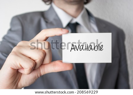 Available. Businessman in suit with a black tie showing or holding business card