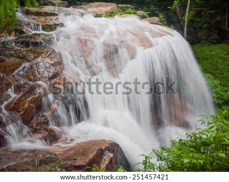 Avalanche Falls, a beautiful New Hampshire waterfall, flows at the top of The Flume Gorge in Franconia Notch State Park. - stock photo