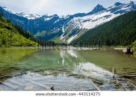 Avalanche Lake - A spring view of clear Avalanche Lake surrounded by high mountain peaks at Glacier National Park, Montana, USA.  - stock photo