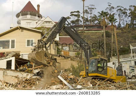 Avalon, CA, USA - November 14, 2014: Tracked excavator tearing down an old house harbor at the port of Avalon on Catalina Island, California - stock photo