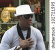 AVENTURA, FLORIDA, USA  - MARCH 11:  Dennis Rodman is enjoying conversation in an outdoor restaurant in Aventura, Florida on March 11, 2013.  Colorful items from a shop window are in the background. - stock photo
