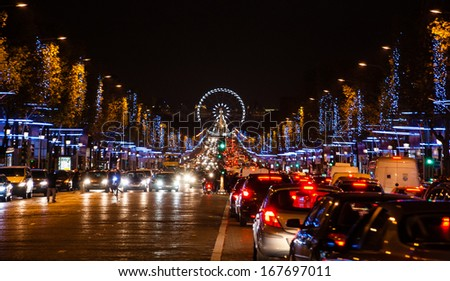 Avenue des Champs-Elysees in Paris decorated with Christmas illumination and the ferris wheel at horizon.