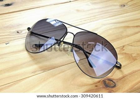 Aviator sunglasses on a wooden board, Classic sunglasses. - stock photo
