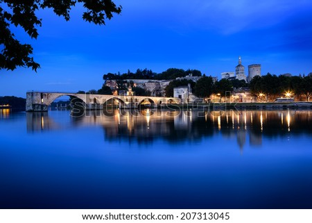 Avignon Bridge, France, viewed at night.  With the Papal Palace. - stock photo