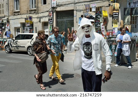 AVIGNON, FRANCE - JUL 12, 2014: Unidentified masked actor performs in the street, to advertise theater show, during the annual Avignon Theater Festival in Avignon