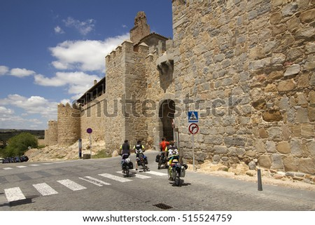 Avila, Spain - May 31, 2016: Cyclists laden with luggage stop at a gate in the ancient city wallls of Avila, Spain on May 31, 2016